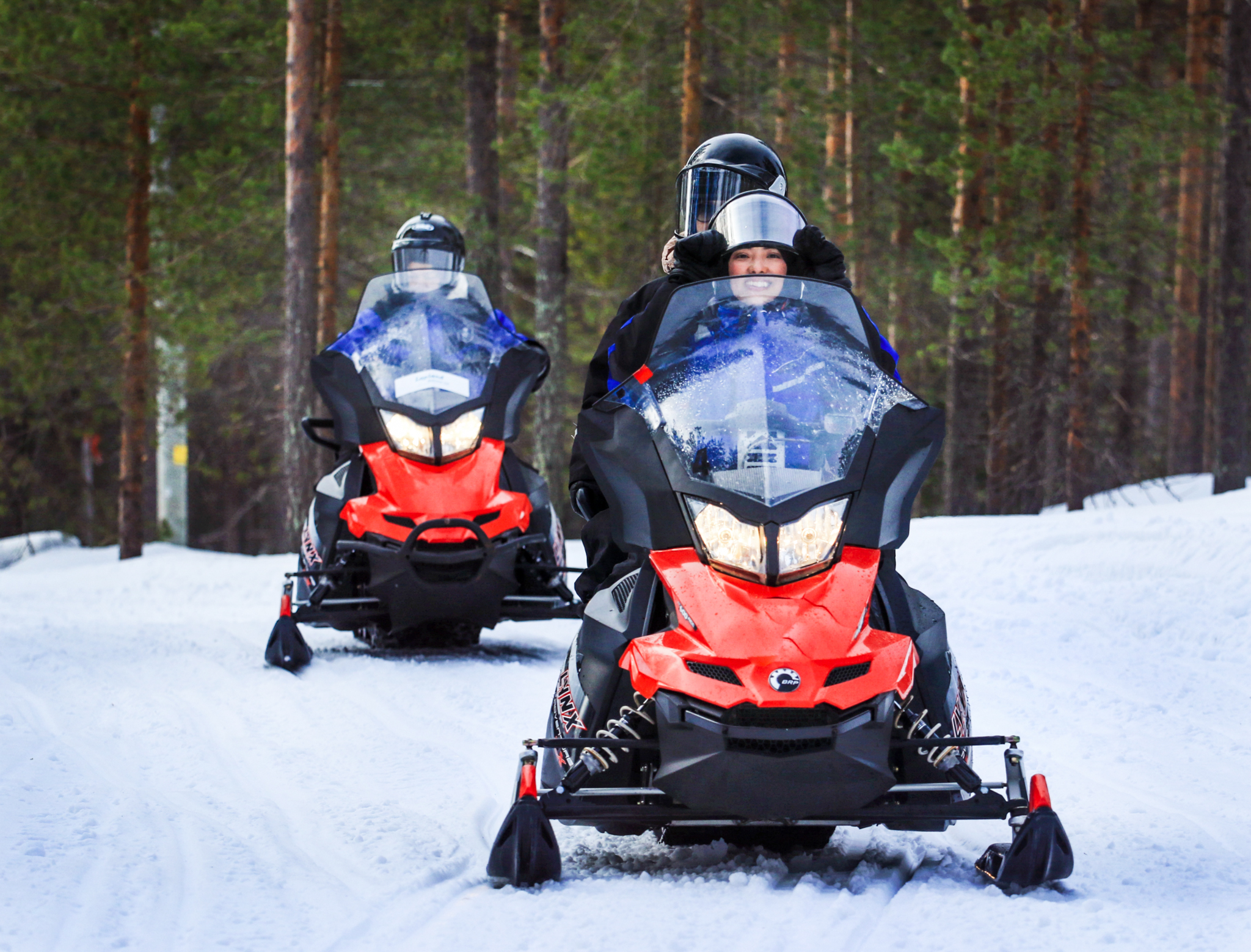 people sitting on snowmobiles