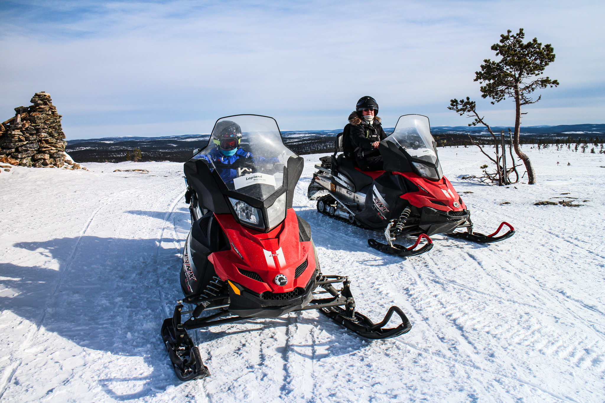 two people sitting on snowmobiles with landscape in background