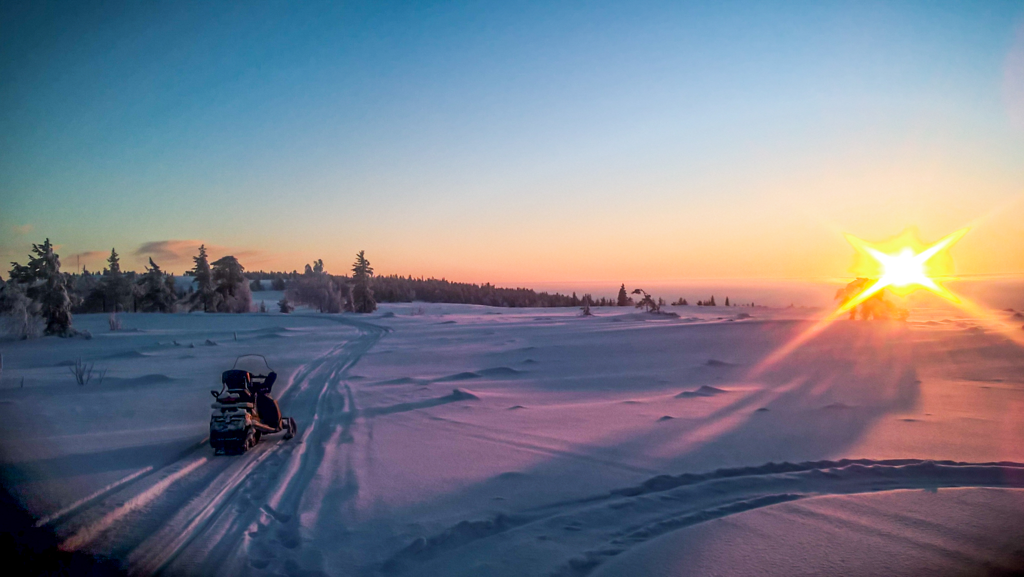 snowmobile in snowy landscape and sunset