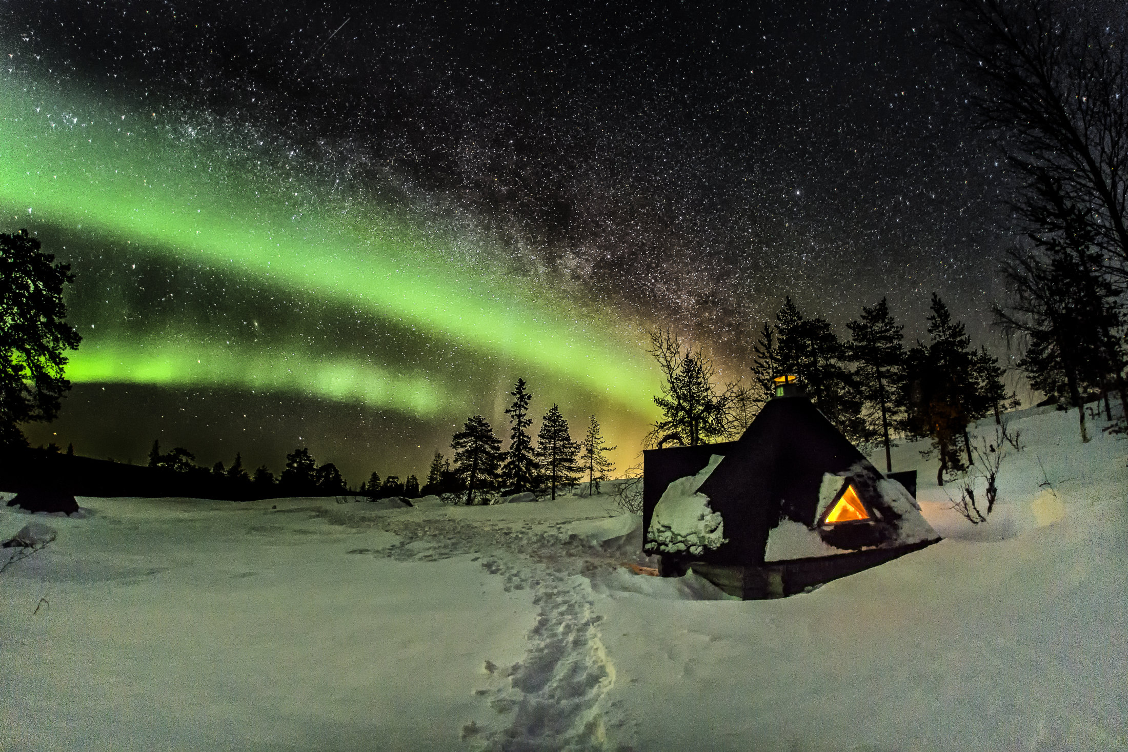 dark sky with bright stars and green northern lights and a wooden tepee