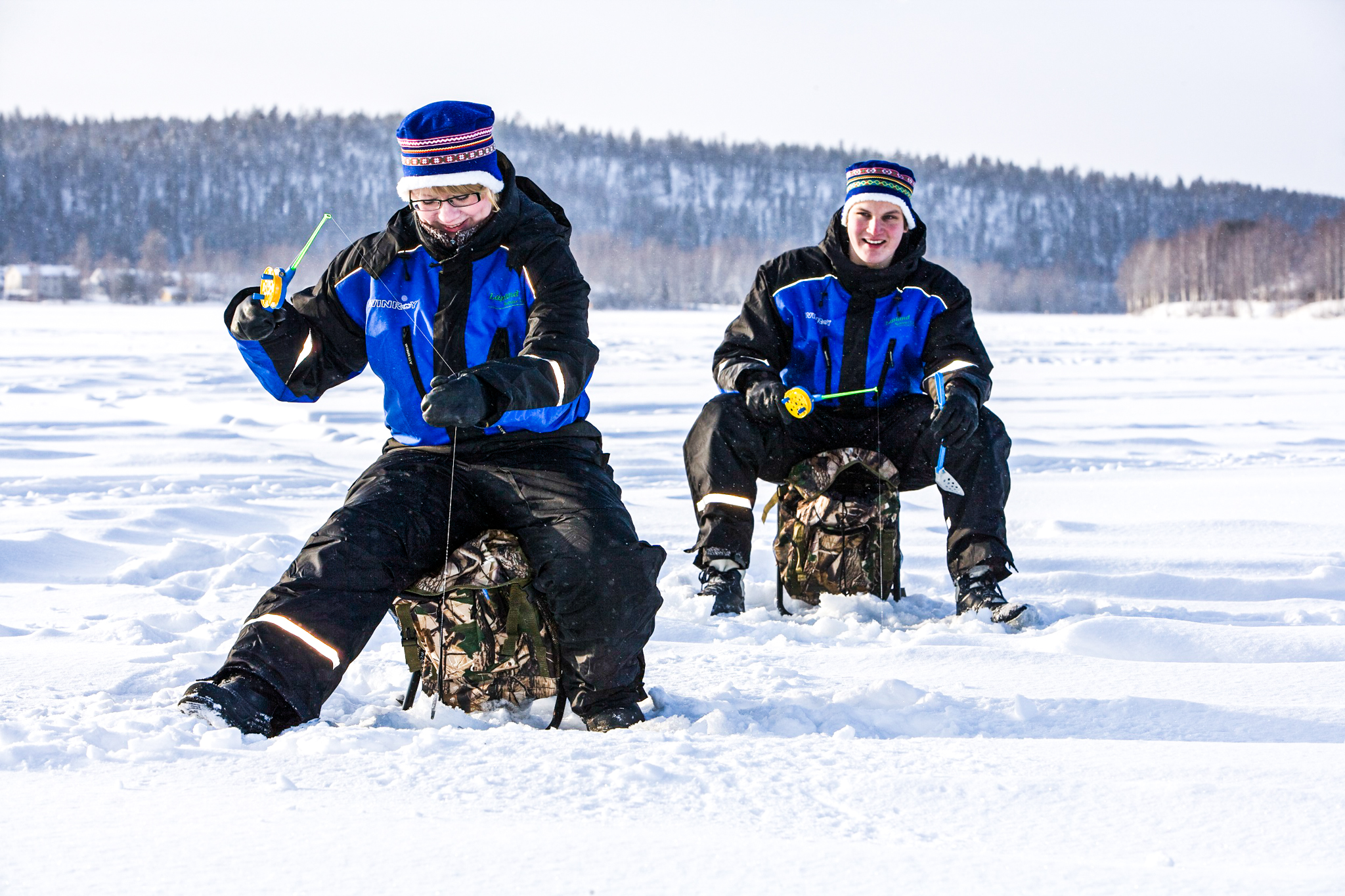 two people during ice fishing on a frozen lake