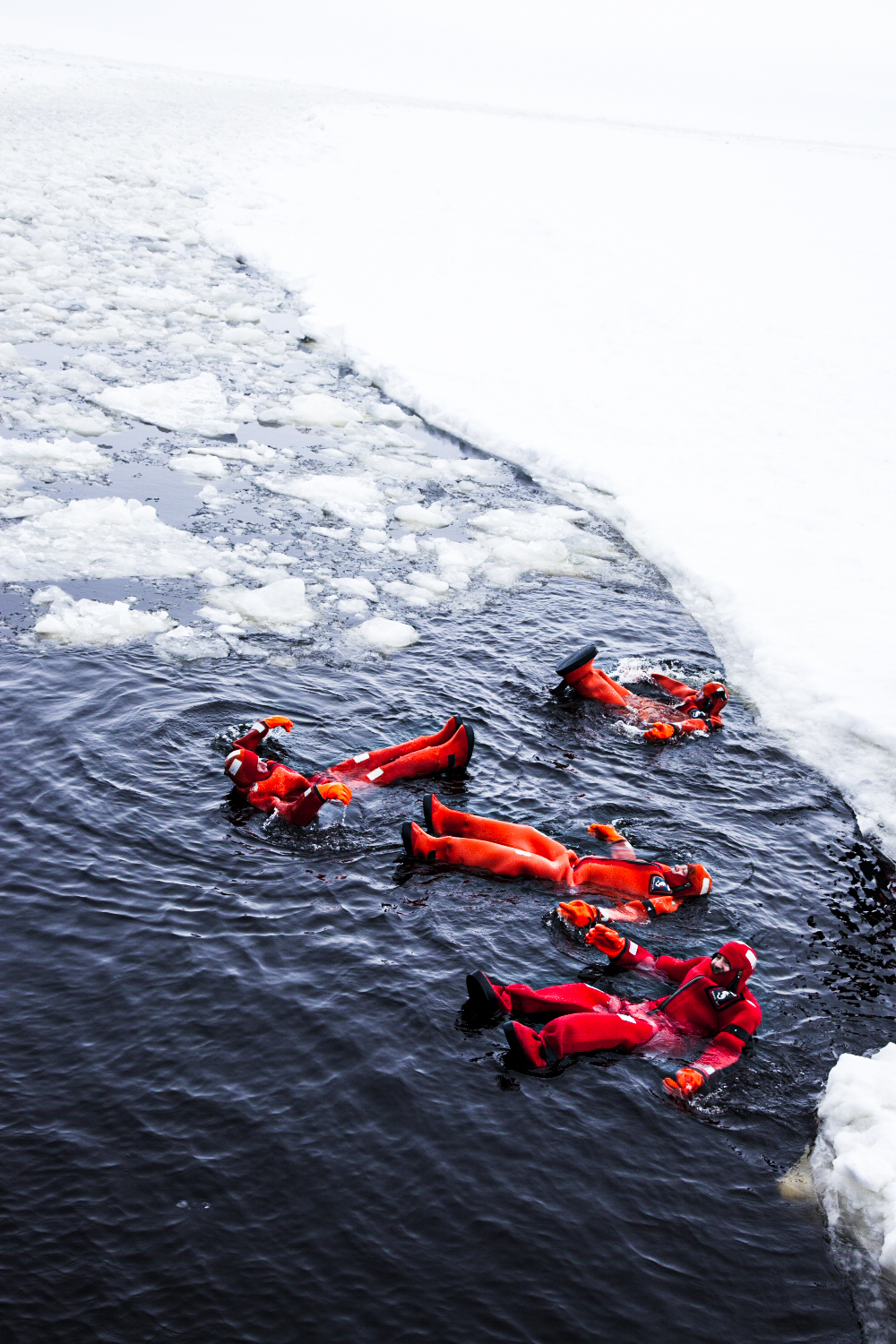 people in survival suits floating in ice water