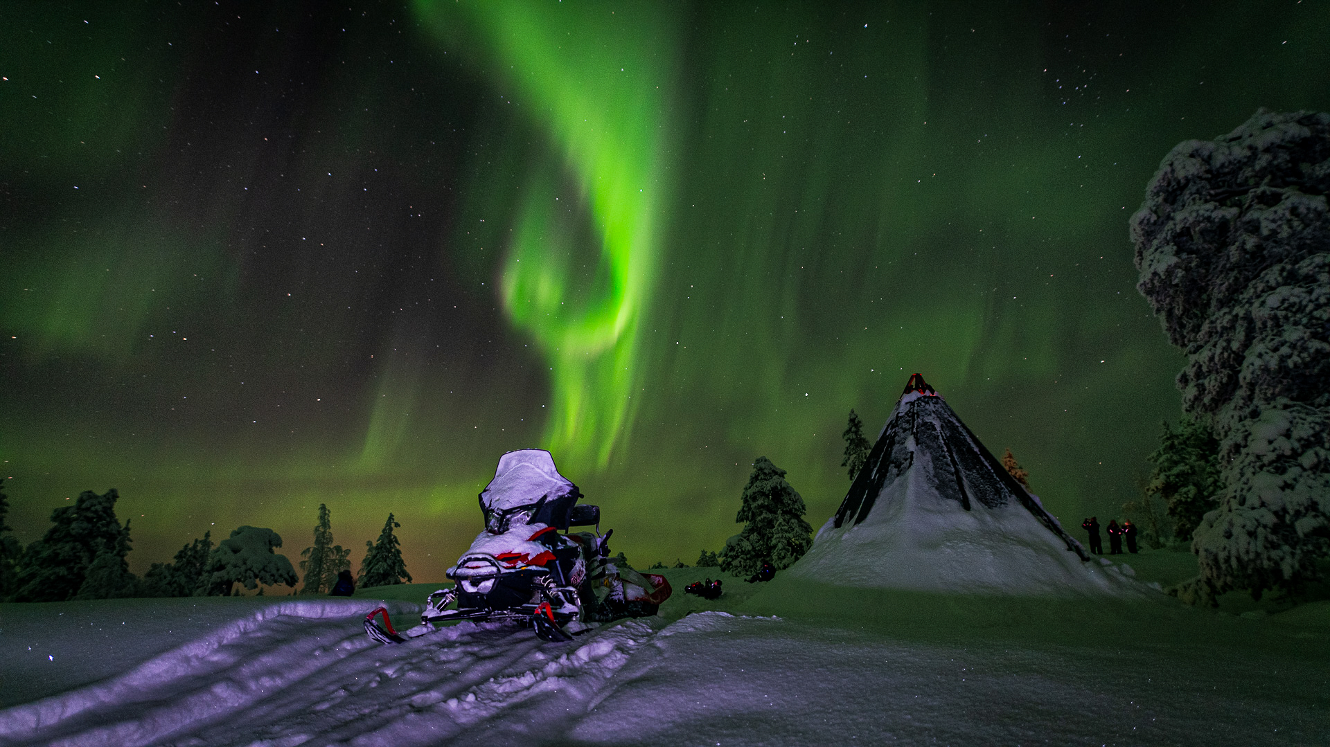snowmobile under northern lights