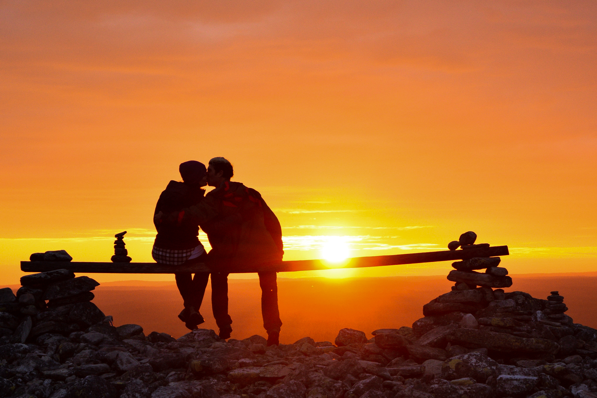 two people kissing on bench at midnight sun