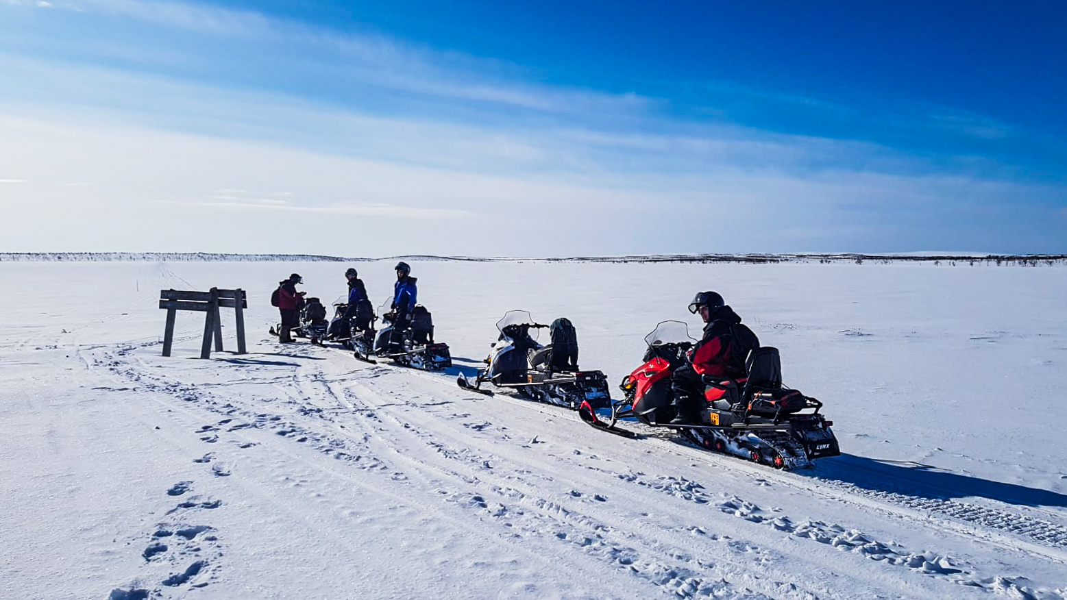 people on snowmobiles and snowy landscape