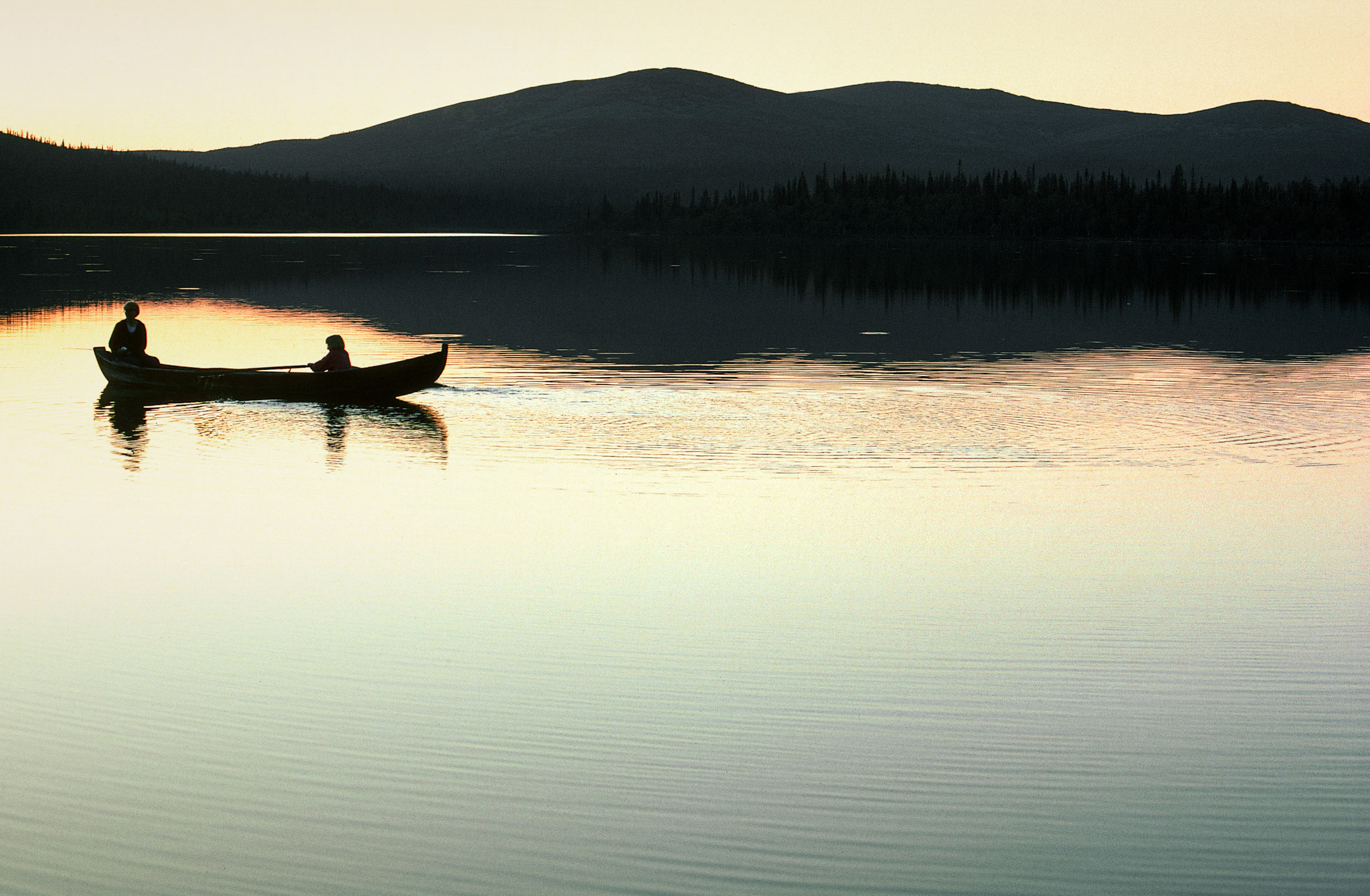two people paddling in kanu on a lake in evening