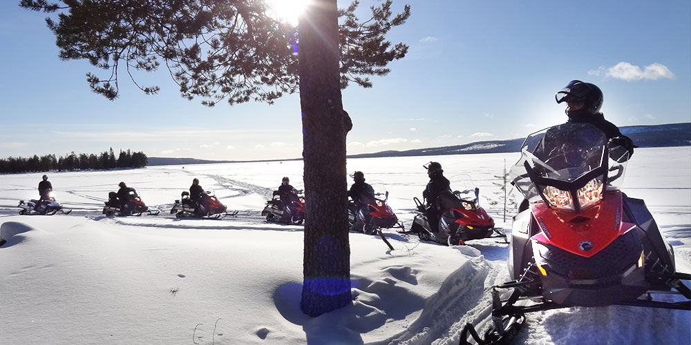 people on snowmobiles on a sunny day