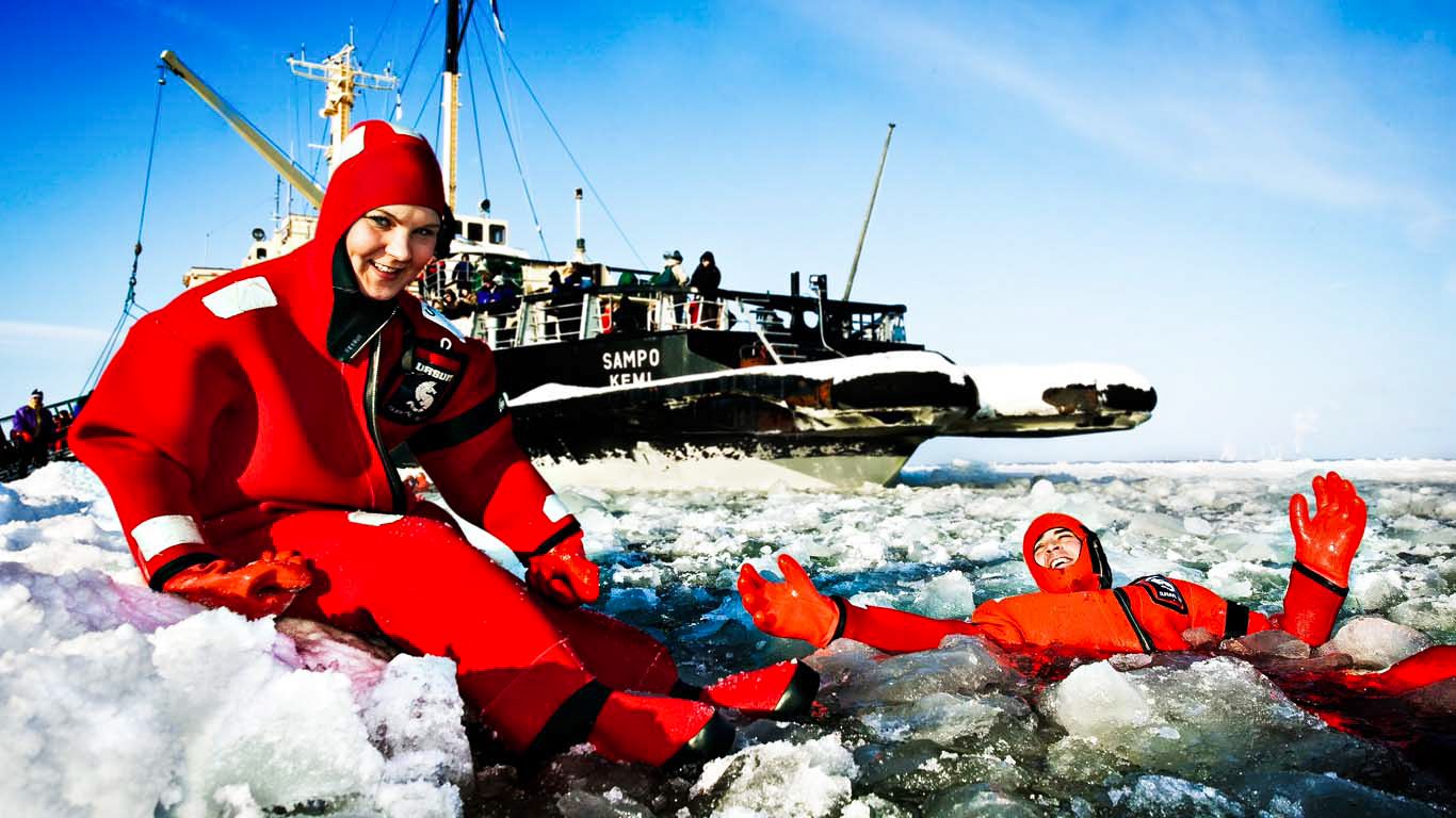 two people in survival suits in front of ice breaker